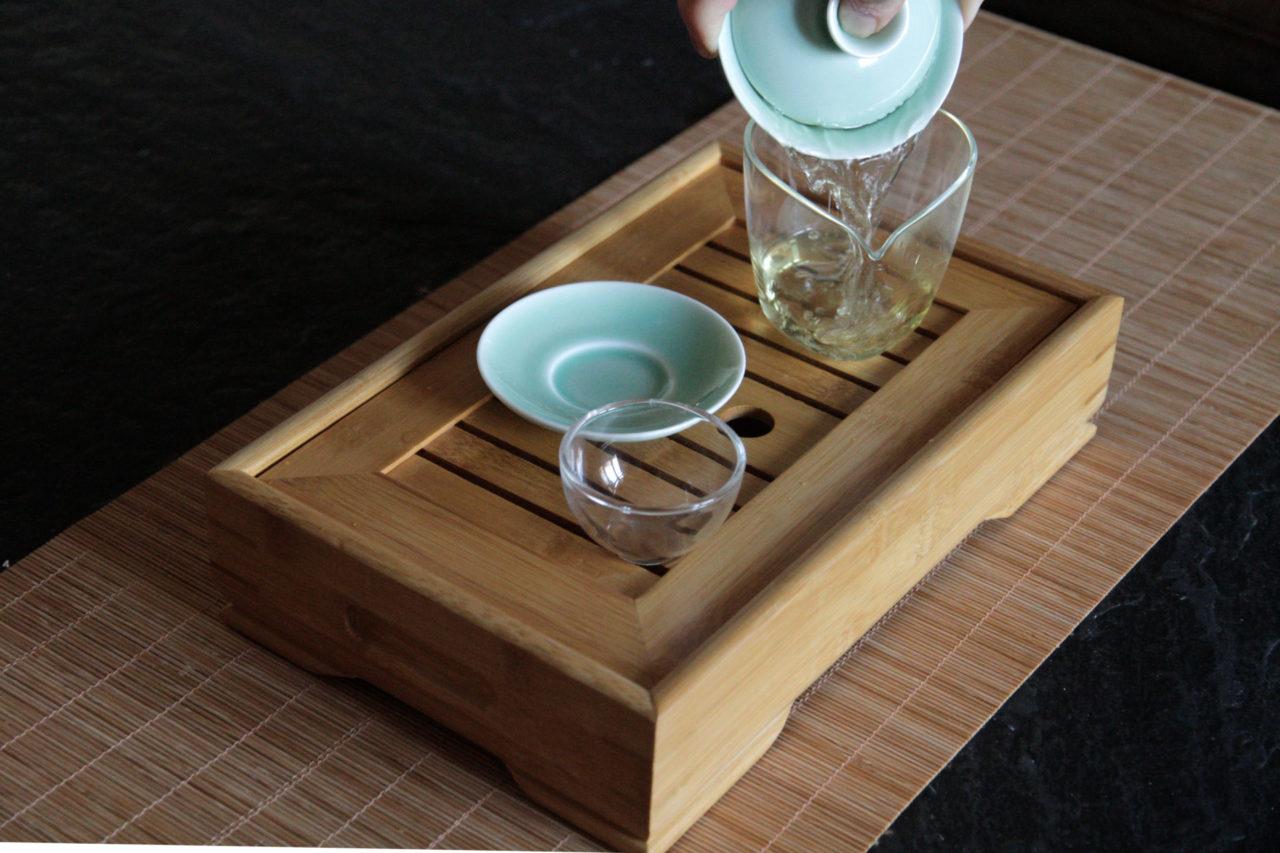 chinesischen tee zubereiten auf traditionelle art mit gaiwan, kännchen, bambustablett, gongfu cha