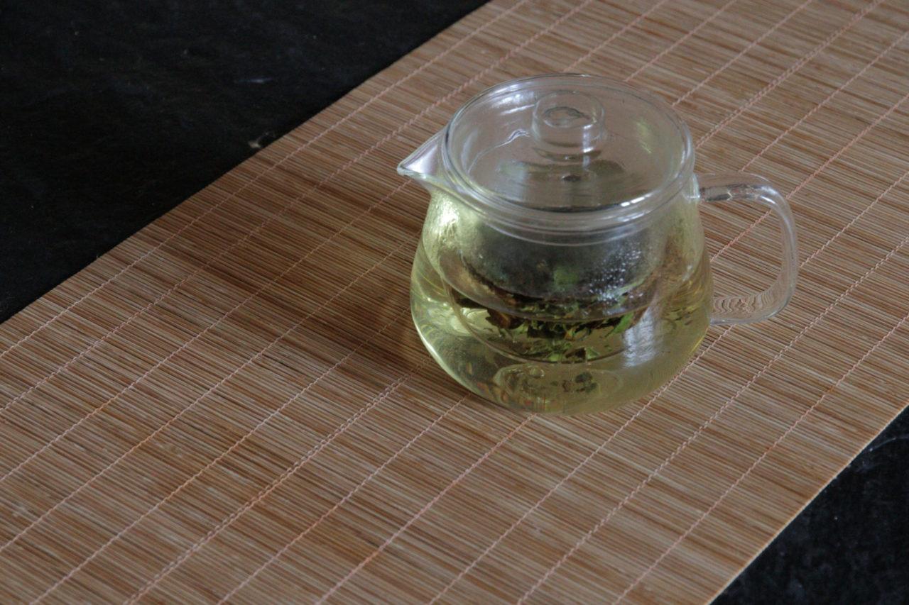 chinesischen tee kochen in kleiner teekanne aus glas mit sieb tee zubereiten